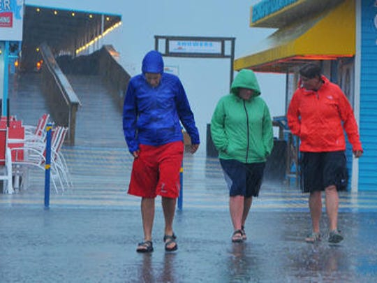 ew brave the bands of blistering rain that are coming off Trpical Storm Colin as they visit the Cocoa Beach Pier Monday evening.