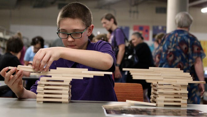 Aaron Green builds a building using wooden blocks at the grand opening of STEAM Central at Stephen's Central Library Thursday, March 23, 2017.