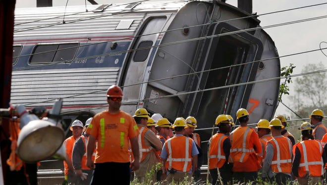 Emergency personnel gather near the scene of a deadly train derailment May 13, 2015, in Philadelphia.