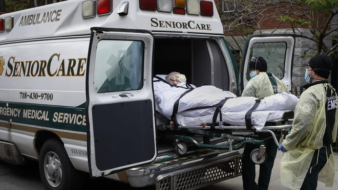In this April 17, 2020, file photo, a patient is loaded into an ambulance by emergency medical workers outside Cobble Hill Health Center in the Brooklyn borough of New York. The nursing home with multiple deaths from the coronavirus has become another glaring example of the struggle to control such outbreaks amid shortages of staff, protective equipment and testing.