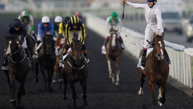 Toast of New York from the U.S., right, ridden by Jamie Spencer, crosses the finish line to win the UAE Derby, a horse race held on the Dubai World Cup day at Meydan Racecourse in Dubai, United Arab Emirates, Saturday, March 29, 2014. (AP Photo/Kamran Jebreili)