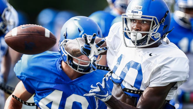 University of Memphis receiver Damonte Coxie (right) makes a catch in front of teammate linebacker Tyler Garvey (left) during a recent practice.
