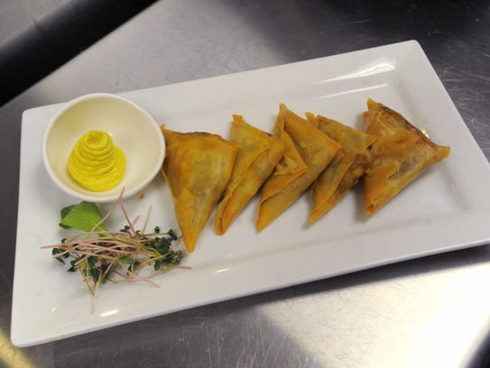 Veggie samosas are filled with potatoes, peas, corn