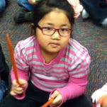 Crestview kindergartner Cheri Cing uses rhythm sticks in music class.