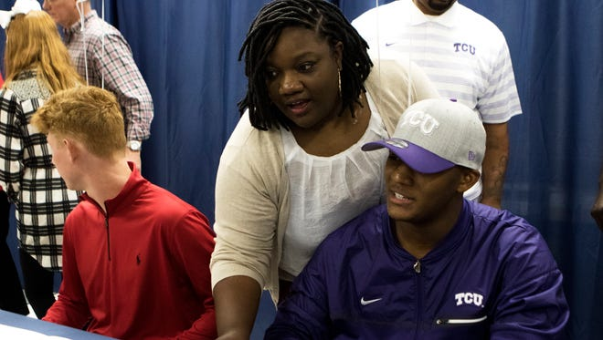 West Monroe defensive tackle Dennis Collins smiles for a television camera while his mother Sherrica Collins leans over his shoulder to sign his contract with Texas Christian University on National Signing Day on Wednesday, February 1, 2017.