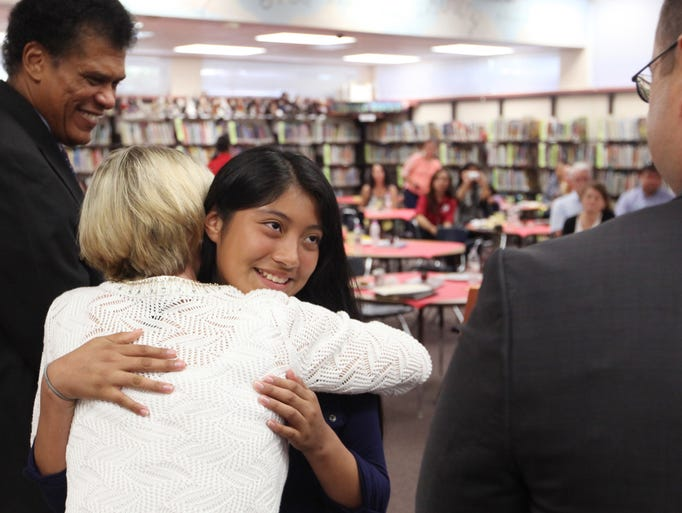 Yesenia Vasquez, of Three Oaks Elementary School, hugs Lucy Davis, of BB&T Bank, after receiving a certificate for completing the requirements of the Self-Reliance Club on Tuesday. Vasquez has earned a savings bond in the amount of $25 through BB&T Bank.