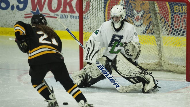 Harwood's Lilianna Ziedins (21) takes a shot on Burlington-Colchester goalie Jenna Blondin (1) during a girls hockey game on Wednesday afternoon.