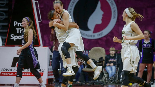 Members of the Iowa City West girls basketball team celebrate in the final seconds after holding on to beat Waukee during the Iowa high school girls state basketball tournament on Wednesday, March 1, 2017, at Wells Fargo Arena in Des Moines.