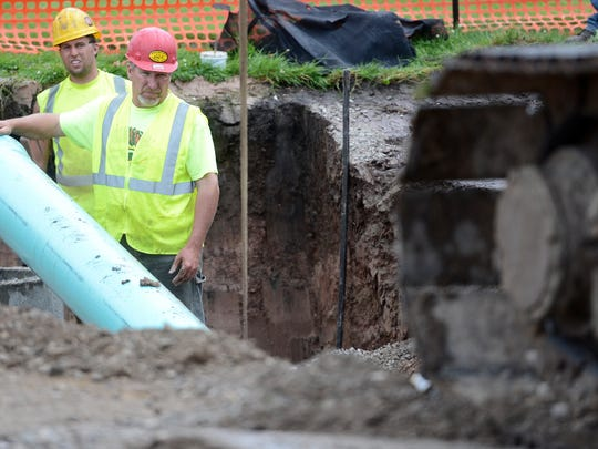 Contractors work below ground level as construction continues Tuesday on Monroe Avenue in Green Bay.