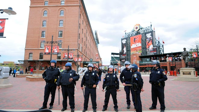 Baltimore police officers stand outside Camden Yards  prior to the cancellation of the game between the Chicago White Sox and Baltimore Orioles.
