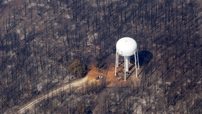 In this Sept. 7, 2011, aerial file photo, an area destroyed by wildfire surrounds a water tower in Bastrop, Texas. The changing landscape of Texas, driven by millions of new residents and the spread of exurbia, has coincided with an unprecedented wave of large wildfires that are occurring more regularly, according to a top state fire official. A nexus of drought, consistent development and profound changes in the way Texas land is used has pushed the state into a new era of firefighting, one marked by combatting bigger fires that are more threatening and damaging.