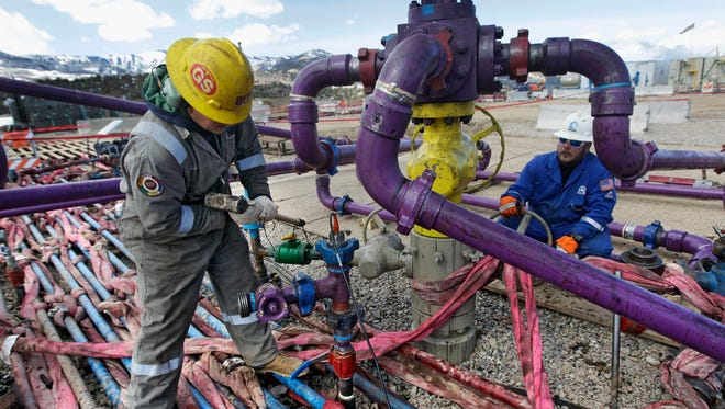 Workers tend to a well head during a hydraulic fracturing operation outside Rifle in western Colorado.