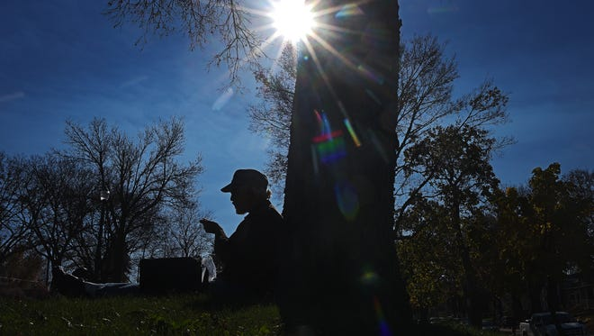"""Dennis Lehmann, of the Freeman, S.D., area, takes advantage of a sunny November afternoon by taking his lunch break under a tree at Lyon Park Thursday, Nov. 3, 2016, in Sioux Falls. Lehmann was in Sioux Falls Thursday delivering raw organic milk for a farmer near Freeman, he said. Lehman said he usually finds a park to take his lunch break in if it's warm enough. """"Depends which park I'm closest to,"""" he said while listing off some of the parks he's stopped at."""