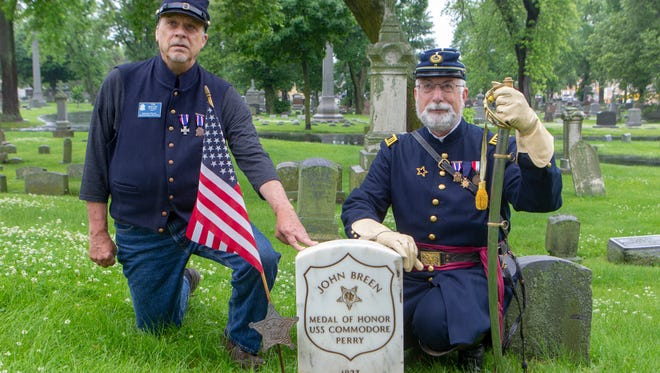 Tom Mueller (left) and Dean Collins of C.K. Pier Badger Camp #1 Milwaukee pose by the headstone of Civil War Medal of Honor recipient John Breen in Calvary Cemetery.