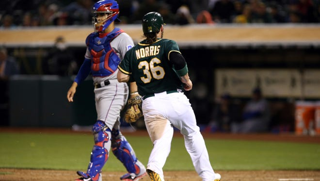 Oakland Athletics catcher Derek Norris (36) scores a run ahead of Texas Rangers catcher Robinson Chirinos (61) during the seventh inning at O.co Coliseum.