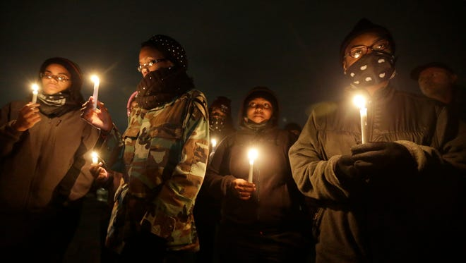 Young women attend a candlelight vigil for victims of gun violence Oct. 10, 2014, in Ferguson, Mo.