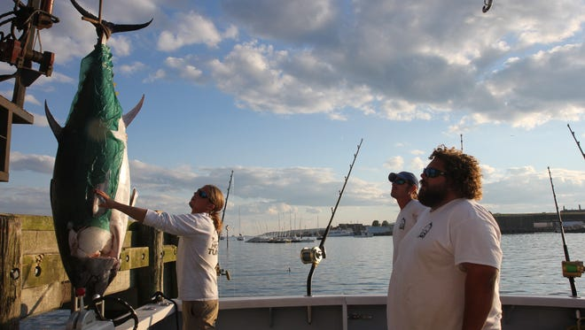 First Mate Jarrett Przybyszewsk guides a tuna into a fish drop, while Deckhand Ryan Bennett and Captain TJ Ott look on.