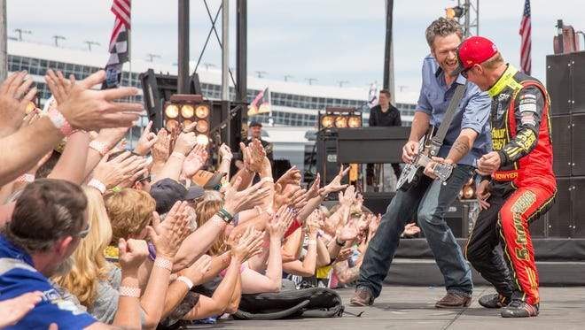 Blake Shelton performs as Clint Bowyer adds some air guitar during the opening of NBC's new video for NASCAR coverage.