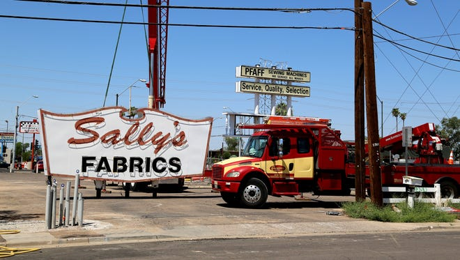 After 56 years atop 24-foot poles, the Sally's Fabrics neon sign was carefully lowered to the ground as it was prepared to be transported to safe storage.