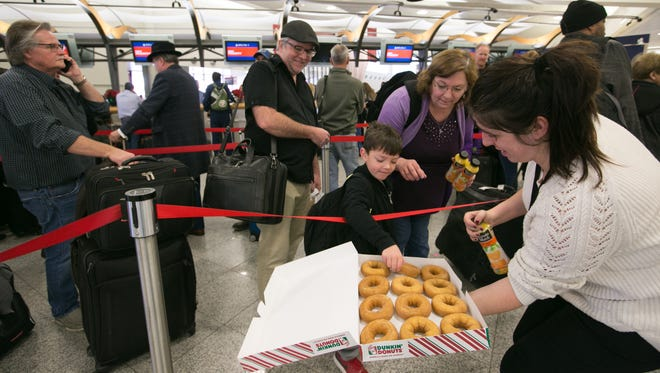 A Delta employee passes out doughnuts and juice to passengers at Hartsfield-Jackson Atlanta International Airport on Dec. 18, 2017. Hundreds of flights were cancelled after a power outage at the airport.