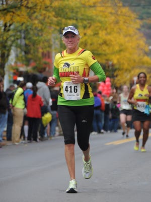"Theresa Connors runs in the Wineglass Marathon in Corning, New York, wearing her Marathon Maniacs jersey proudly. ""No matter where you go, you have running friends,"" she says, noting she has already signed up for three more marathons."