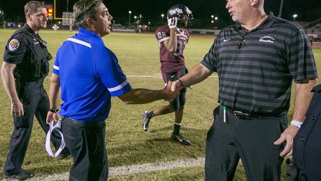Chandler High coach Shaun Aguano shakes hands with Chandler Hamilton coach Steve Belles after Chandler won their high school football game Oct. 2. The coaches and their teams face off in Friday's Division I championship game.