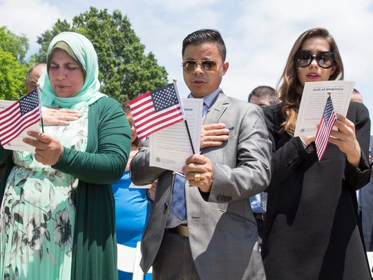 Citizenship candidates observe the pledge of allegiance