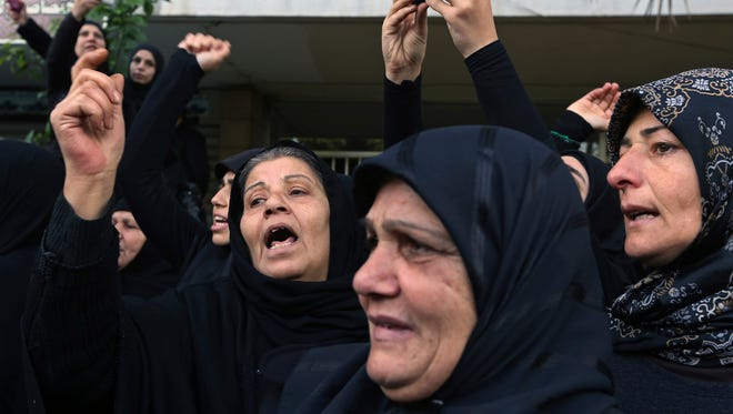 Lebanese women mourn as they look towards the coffin of Jihad Mughniyeh, the son of Imad Mughniyeh, a top Hezbollah operative assassinated in 2008 in Damascus and one of the six Hezbollah fighters killed in what the group said was an Israeli airstrike Sunday in the Golan, during his funeral procession, in southern Beirut, Lebanon, Monday, Jan. 19, 2015. Jihad Mughniyeh is the Hezbollah's most prominent figure to die so far in Syria since the Shiite militant group joined the conflict next door in 2012, fighting on Syrian President Bashar Assad's side against the Sunni-led rebellion.