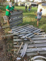 Boy Scouts and leaders from the Boy Scouts of America Riverside District dismantle a hurricane-damaged fence for a 90-year-old Indian Harbour Beach homeowner.