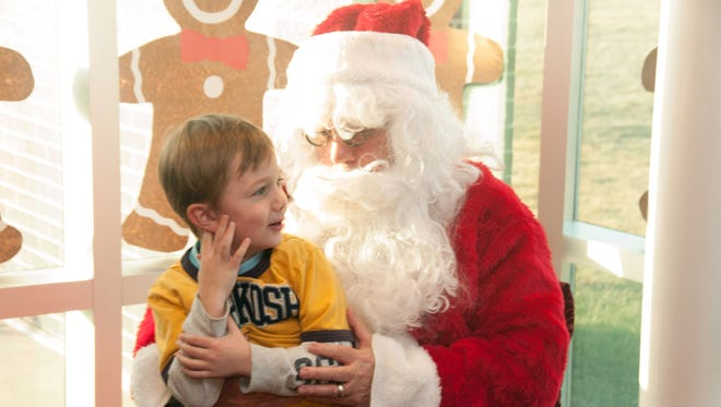 Grayson McAndrew, 6, of Urbandale, chats with Santa Claus, Saturday, Dec. 7, 2013, at the Johnston Public Library's town holiday celebration.