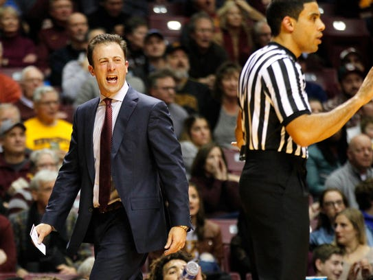 Minnesota head coach Richard Pitino, left, argues about