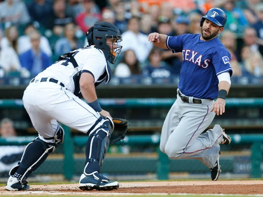 Texas Rangers' Mitch Moreland, right, slides safely past Detroit Tigers catcher James McCann to score on a Elvis Andrus double in the second inning of a baseball game Friday, May 6, 2016, in Detroit. (AP Photo/Paul Sancya)
