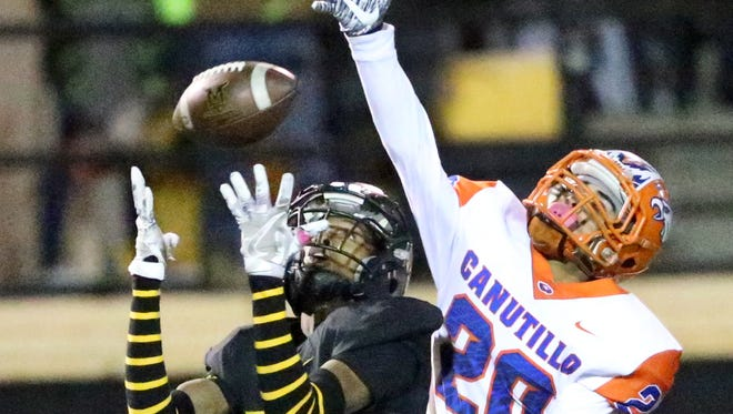 Parkland wide receiver De'quan Henderson, 13, catches a long throw despite the efforts of Nathan Martinez, 20, of Canutillo Friday night. The play set up a successful field goal.