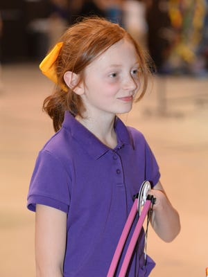 Savannah Strain smiles while practicing with the archery team at Benton Elementary School.