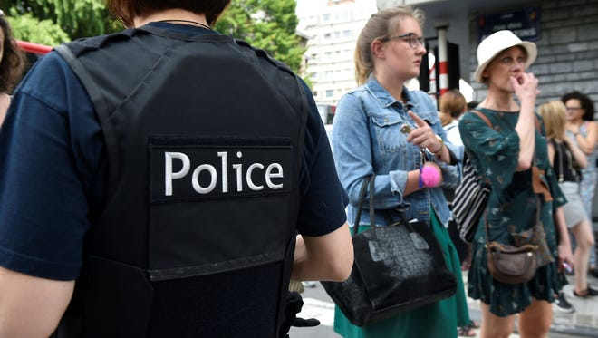 A police officer speaks with parents of children at a nearby high school in the eastern Belgian city of Liege on May 29, 2018, after a gunman shot dead three people, two of them policemen, before being killed by elite officers.