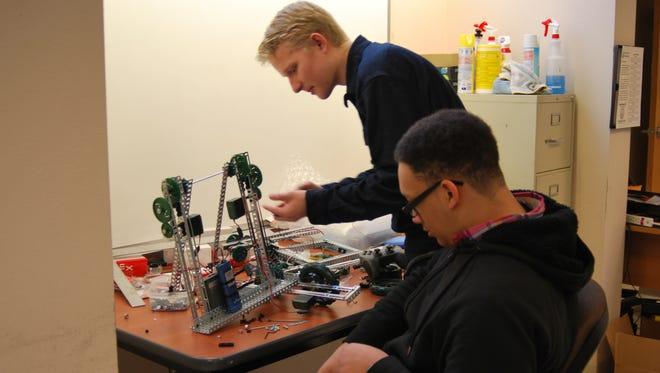 Navajo Prep freshman Nathan Henry, sitting, and junior Xander Jones work on Henry's robot at the school on Feb. 8.