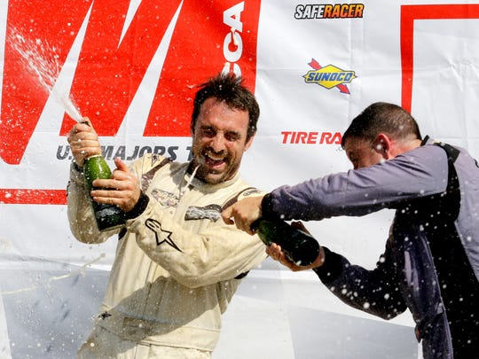 Spec Racer Ford winner David Dickerson gets sprayed by champagne by third place finisher Greg Obadia in victory circle at Watkins Glen International during the SCCA U.S. Majors Tour on Sunday.