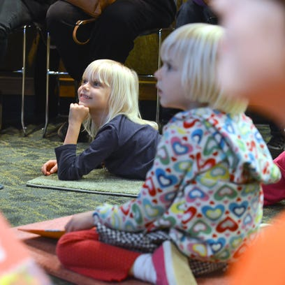 Seven-year-old Ruth Dodd, center, listens as author