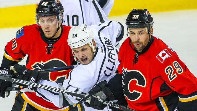 Los Angeles Kings left wing Kyle Clifford and Calgary Flames center Markus Granlund and defenseman Deryk Engelland fight for position at Scotiabank Saddledome.
