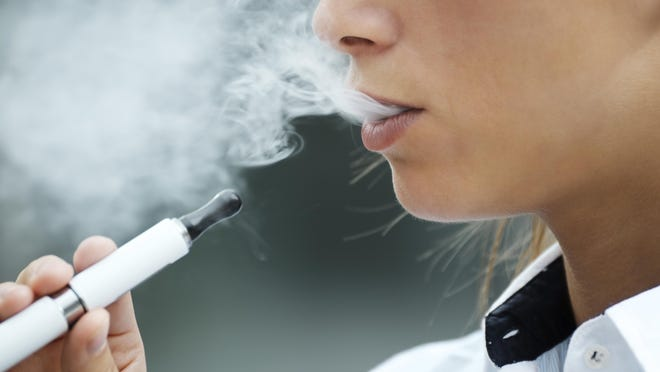 Close up of a young adult smoking an e-cigarette