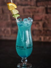 A drink known as an Adios combines vodka, gin, white rum and blue Curacao in an ice-filled hurricane glass. Fill the glass with equal parts sour mix and 7-Up, garnish, and serve.