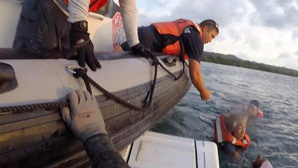 Michael Orr, a University of Guam professor, assisted four males on a sailboat that ran aground in Agat reach a Guam Fire Department rescue boat Monday, Feb. 6, 2018.