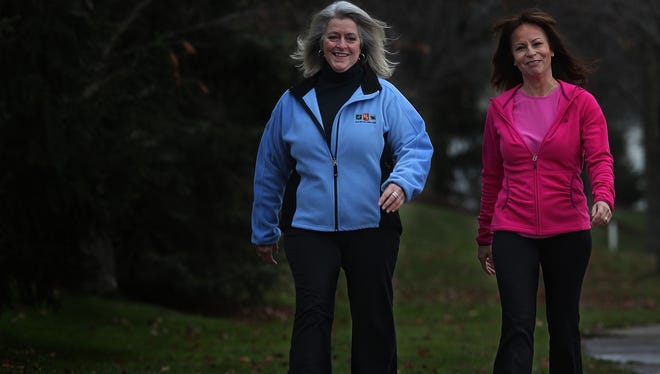 Jean Bourgeois, right, CEO of Excelsas, walks with employee Cyndi Takacs as part of the company walking program. The program encourages health in her employees through walking.