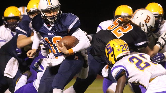 Blackman's quarterback Miller Armstrong  (12) runs the ball as Smyrna's Nick Okeke (11) tries to pull Miller down and Smyrna's Ian Cleveland (20) moves in for a second tackle during the game at Blackman, on Friday Oct 2, 2015.