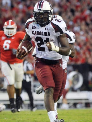 FILE - In this Sept. 10, 2011 file photo South Carolina running back Marcus Lattimore (21) runs for a touchdown against Georgia during the fourth quarter of an NCAA college football game in Athens, Ga. Lattimore says he will undergo knee surgery later this week. South Carolina coach Steve Spurrier said Tuesday, Nov. 15, 2011, that doctors wanted the swelling to go down in the knee and the injuries to stabilize before surgery. (AP Photo/John Amis, File)