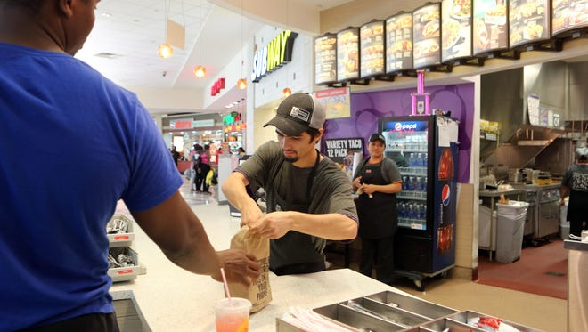 Rob Ozuna, 19, of White Plains serves a customer at Taco Bell/KFC at the Galleria mall in White Plains, July 22, 2015.