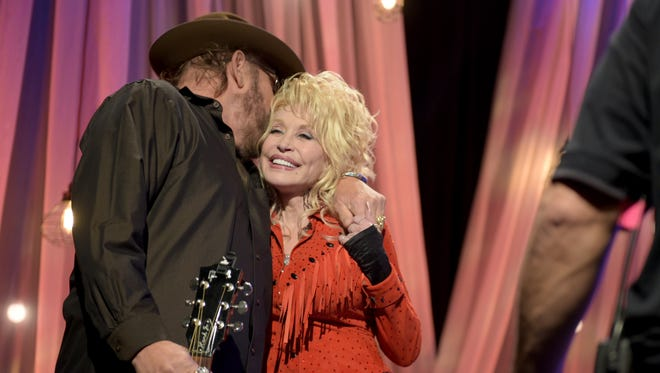 "Hank Williams Jr. hugs Dolly Parton at the pre-taping for the ""Dolly Parton's Smoky Mountains Rise: A Benefit for the My People Fund"" telethon Tuesday, Dec. 13, 2016, in Nashville."