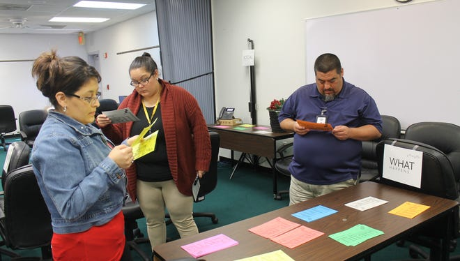 CPS caseworkers read cards during a domestic violence training exercise Monday, Feb. 6, 2017.