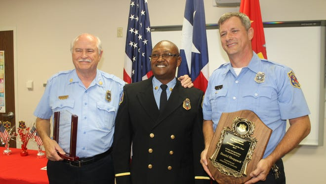 Elvin Bates, left, Captain James Brown and Dan Sheppard share a moment after the fire department's highest honors were announced.