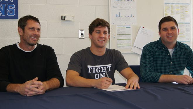 Livonia Stevenson senior swimmer Jackson O'Dowd was joined by his high school coach Jeff Shoemaker (left) and one of his club coaches, Steve Bruestley (right) as he signed a letter of intent to swim for the University of Pennsylvania.
